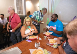 July 12, 2019: — Senator Art Haywood and and fellow legislators serve up food, coffee and drinks to customers during the busy happy hour at El Fuego restaurant in support of the federal Raise the Wage Act nationwide and One Fair Wage in the state.